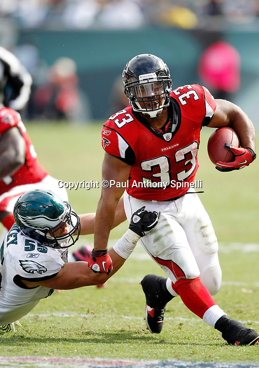 Atlanta Falcons running back Michael Turner (33) runs the ball while pulling away from a tackle attempt by Philadelphia Eagles linebacker Stewart Bradley (55) during the NFL week 6 football game against the Philadelphia Eagles on Sunday, October 17, 2010 in Philadelphia, Pennsylvania. The Eagles won the game 31-17. (©Paul Anthony Spinelli)