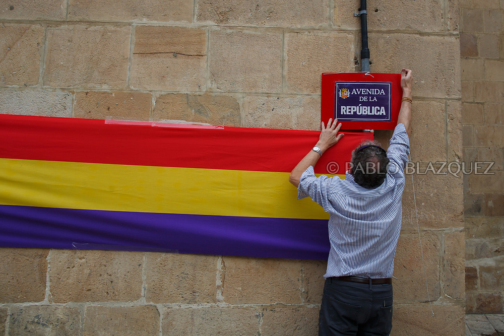 14/04/2018. A man hangs a placard reading 'Avenida de la Republica' next to a Republican Spanish flag during a ceremony to deliver the remains of victims of Spain Civil War exhumed in Cobertelada and Calata&ntilde;azor to their relatives on April 14, 2018 in Soria, Spain. La Asociacion Soriana Recuerdo y Dignidad (ASRD) 'The Soria Association for Memory and Dignity' celebrated a tribute to hand over the remains of civil war victims to their families. The Society of Sciences of ARANZADI helped with the research, exhumation and identification of the bodies, after villagers passed the information about the mass grave, 81 years after the assassination took place, to the ASRD. Seven people were assassinated around August 25, 1936 by Falangists, as part of General Francisco Franco armed forces, and buried in the 'Fosa de los Maestros' (Teachers Mass Grave) near Cobertelada, Soria, after being taken from prison of Almazan during the Spanish Civil War. Five of them were teachers in the region, and also friends of Spanish writer Antonio Machado. The other two still remain unidentified. Another body was assassinated by Falangists accompanied by a priest in 1936, and was exhumed on 23 September of 2017 near Calata&ntilde;azor, Soria. It belonged to Abundio Andaluz, a politician, lawyer and musician in Soria.<br /> Spain's Civil War took the lives of thousands of people on both sides, and civilians. But Franco continued his executions after the war has finished. Teachers, as part of the education sector, were often a target of Franco's forces. Spanish governments has never done anything to help the victims of the Civil War and Franco's dictatorship while there are still thousands of people missing in mass graves around the country. (&copy; Pablo Blazquez)