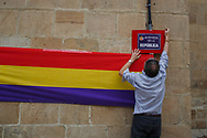 14/04/2018. A man hangs a placard reading 'Avenida de la Republica' next to a Republican Spanish flag during a ceremony to deliver the remains of victims of Spain Civil War exhumed in Cobertelada and Calatañazor to their relatives on April 14, 2018 in Soria, Spain. La Asociacion Soriana Recuerdo y Dignidad (ASRD) 'The Soria Association for Memory and Dignity' celebrated a tribute to hand over the remains of civil war victims to their families. The Society of Sciences of ARANZADI helped with the research, exhumation and identification of the bodies, after villagers passed the information about the mass grave, 81 years after the assassination took place, to the ASRD. Seven people were assassinated around August 25, 1936 by Falangists, as part of General Francisco Franco armed forces, and buried in the 'Fosa de los Maestros' (Teachers Mass Grave) near Cobertelada, Soria, after being taken from prison of Almazan during the Spanish Civil War. Five of them were teachers in the region, and also friends of Spanish writer Antonio Machado. The other two still remain unidentified. Another body was assassinated by Falangists accompanied by a priest in 1936, and was exhumed on 23 September of 2017 near Calatañazor, Soria. It belonged to Abundio Andaluz, a politician, lawyer and musician in Soria.<br /> Spain's Civil War took the lives of thousands of people on both sides, and civilians. But Franco continued his executions after the war has finished. Teachers, as part of the education sector, were often a target of Franco's forces. Spanish governments has never done anything to help the victims of the Civil War and Franco's dictatorship while there are still thousands of people missing in mass graves around the country. (© Pablo Blazquez)