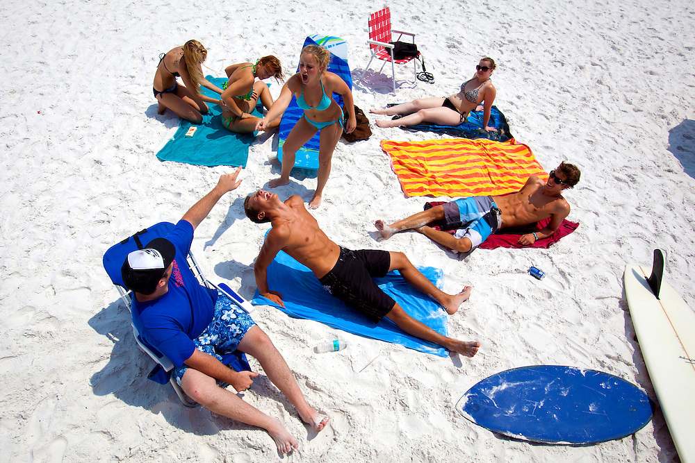 SARASOTA, FL -- June 14, 2011 -- Morgan Swope, 22, clockwise from upper right,  Keith Misja, 18, Mario Petitti, 17, Ben Glucklich, 19, Kali Gough, 17, Allie Harris, 18, and Carrie Swope, 18, lay out in the white sand under the sun at Siesta Public Beach in Sarasota, Fla., on Tuesday, June 14, 2011.