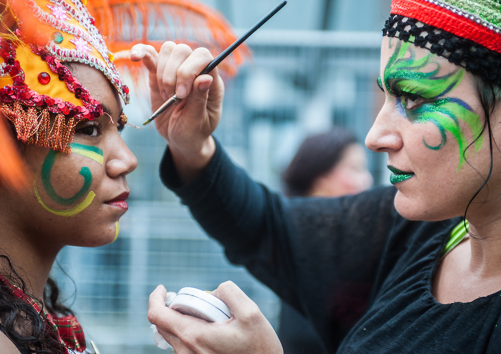 London, UK - 25 August 2014: a woman puts make up on a reveller during the Notting Hill Carnival in London.