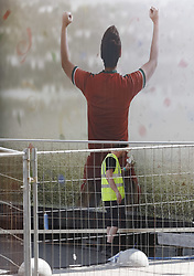 May 18, 2018 - Kiev, Ukraine - A worker cleans a poster in a fan zone of the UEFA Champions League final in central Kiev, Ukraine, 18 May, 2018. The football UEFA Champions League final match between Real Madrid and Liverpool FC next May 26 at the NSC Olimpiyskiy Stadium. (Credit Image: © Str/NurPhoto via ZUMA Press)