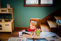 A 2-year-old boy reads the newspaper while having breakfast at his family's dining table.