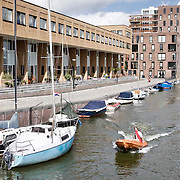 Nederland Amsterdam 15-09-2010 20100915..Nieuwbouw wijk IJburg, woningen in het hogere segment. Jongeman vaart in motorbootje door de wijk, langs de nieuwbouwwoningen en de boten die aan de kade liggen. IJburg is een woonwijk in aanbouw in het oosten van de gemeente Amsterdam, in de Nederlandse provincie Noord-Holland. Kenmerkend aan de in het IJmeer gelegen wijk is dat deze op kunstmatige eilanden is gebouwd. IJburg maakt onderdeel uit van het stadsdeel Oost. Holland, The Netherlands, dutch, Pays Bas, Europe , Yburg, het Ij, Het Y, , waterveiligheid, waterveiligheid en gebiedsontwikkeling, waterwijk, waterwijken, waterwoning, waterwoningen, wijk, wijken, wonen aan het water, woning, woningaanbod, woningbouw, woningen, woningmarkt, woningvoorraad, woonbuurt, woonbuurten, woonlast, woonlasten, woonwijk, woonwijken, zeilboot, zeilbootje..Foto: David Rozing