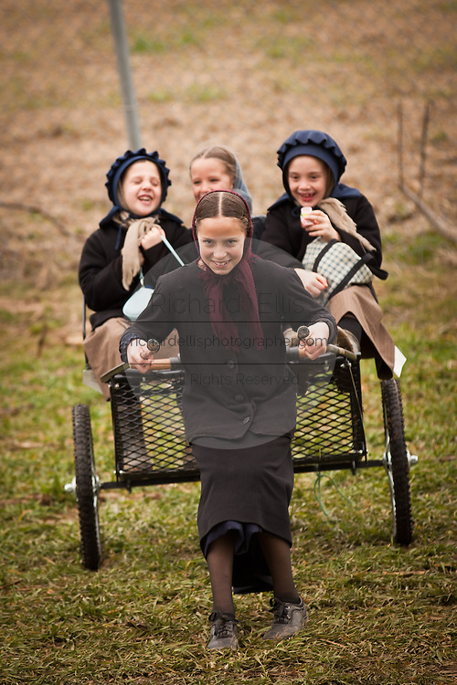 Amish girls play on a carriage during the Annual Mud Sale to support the Fire Department  in Gordonville, PA.