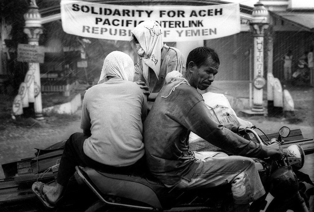 Family face pelting tropical rain as they ride on back of a motorbike through the streets of Banda Aceh.