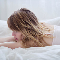Young woman with blonde hair wearing light pink top lying face down in bed on white sheets with arms stretched out in front of her