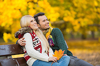 Happy young couple looking away while sitting on park bench during autumn