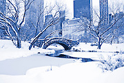 View of Central Park, Gapstow Bridge and the Plaza Hotel, Manhattan, New York City during winter snowstorm.