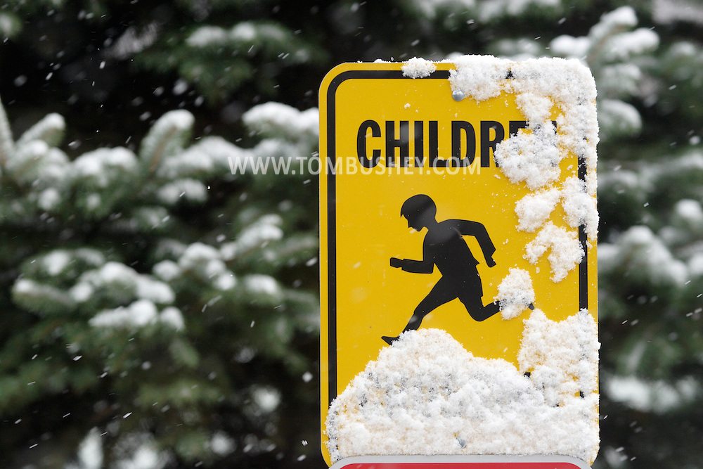 "Middletown, NY - A yellow ""Children Crossing"" sing is partically covered by blowing snow during the first snowfall of the season on Nov. 19, 2007."