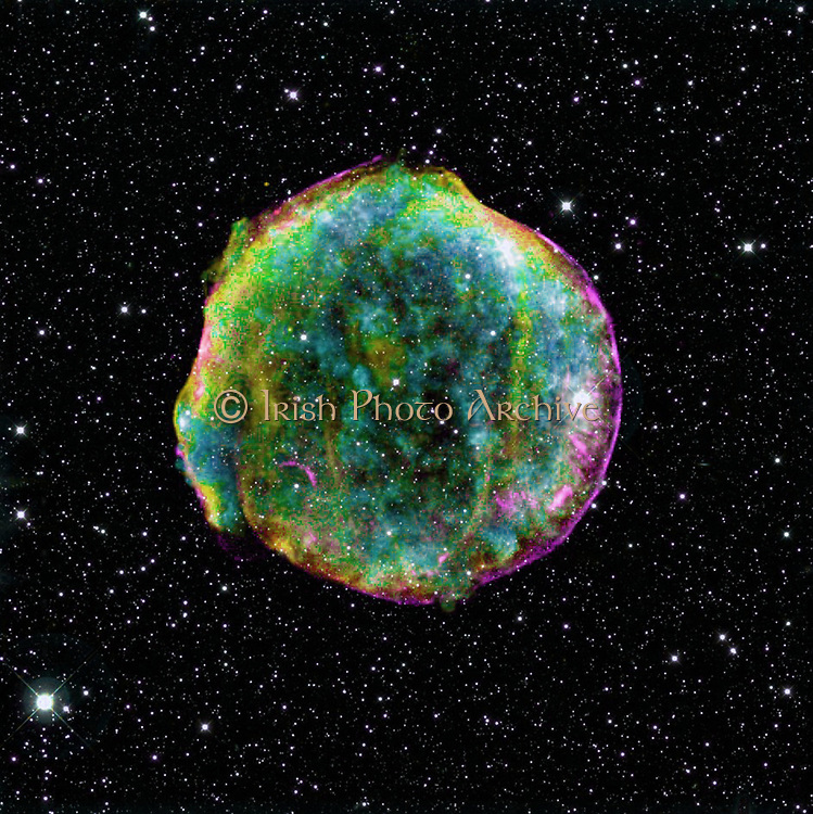composite image of the Tycho supernova remnant combines infrared and X-ray observations obtained with NASA's Spitzer and Chandra space observatories, respectively, and the Calar Alto observatory, Spain. It shows the scene more than four centuries after the brilliant star explosion witnessed by Tycho Brahe and other astronomers of that era. The explosion has left a blazing hot cloud of expanding debris (green and yellow). The location of the blast's outer shock wave can be seen as a blue sphere of ultra-energetic electrons. Newly synthesized dust in the ejected material and heated pre-existing dust from the area around the supernova radiate at infrared wavelengths of 24 microns (red). Foreground and background stars in the image are white.