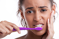Young Mixed Race woman with toothbrush suffering from toothache against white background