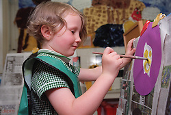 Nursery school girl using paintbrush and easel to paint picture,