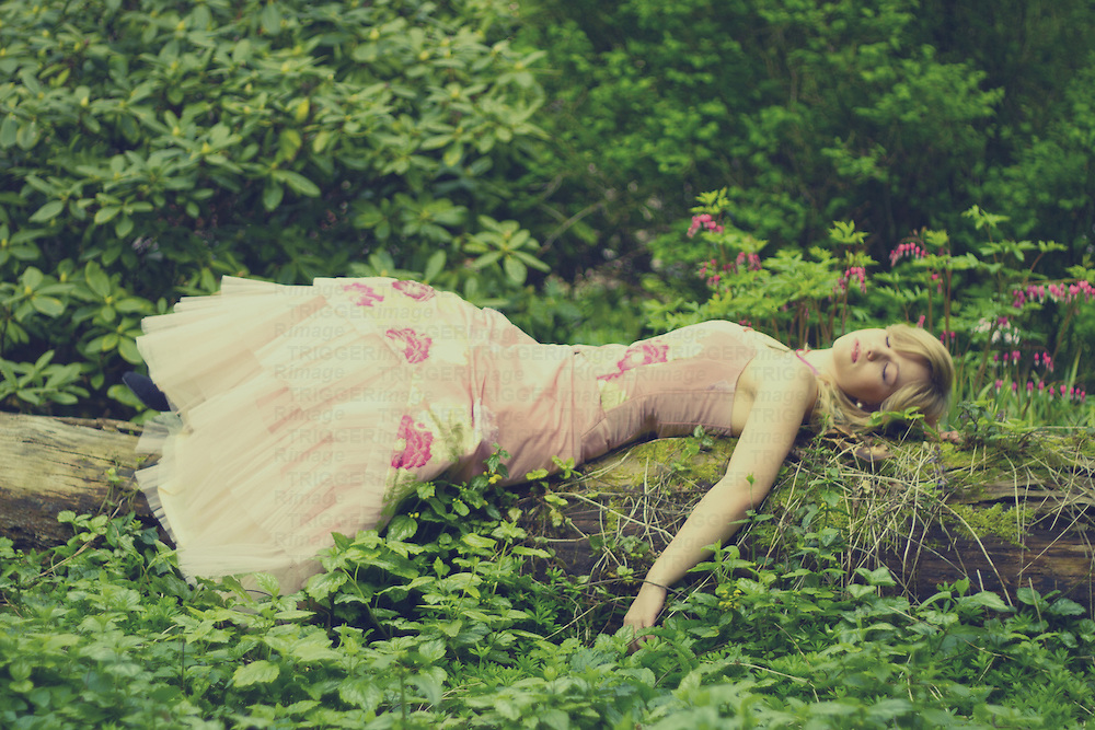 A blonde young adult woman dressed in a fancy rose colured dress sleeping in the garden on a tree trunk