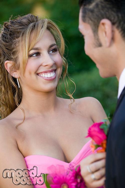 Smiling Teenage Girl Pinning Flower on Date