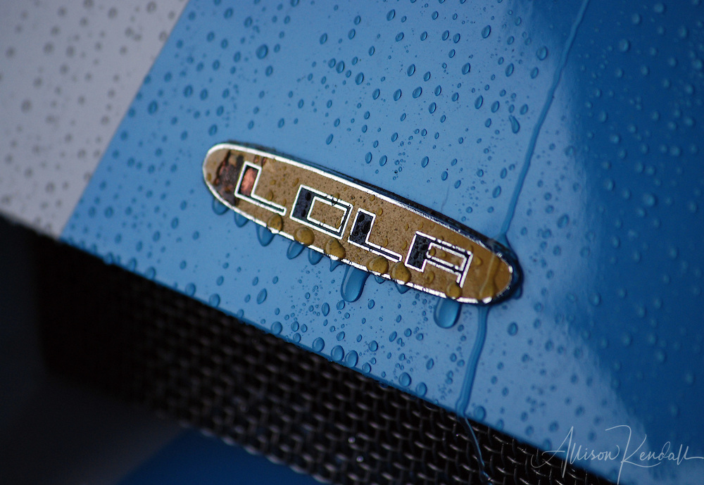Raindrops streak down the hood and badge of a Lola T2-92 vintage automobile racecar