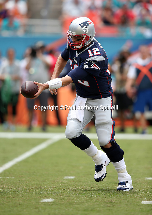 New England Patriots quarterback Tom Brady (12) hands off the ball during the NFL week 1 regular season football game against the Miami Dolphins on Sunday, Sept. 7, 2014 in Miami Gardens, Fla. The Dolphins won the game 33-20. ©Paul Anthony Spinelli