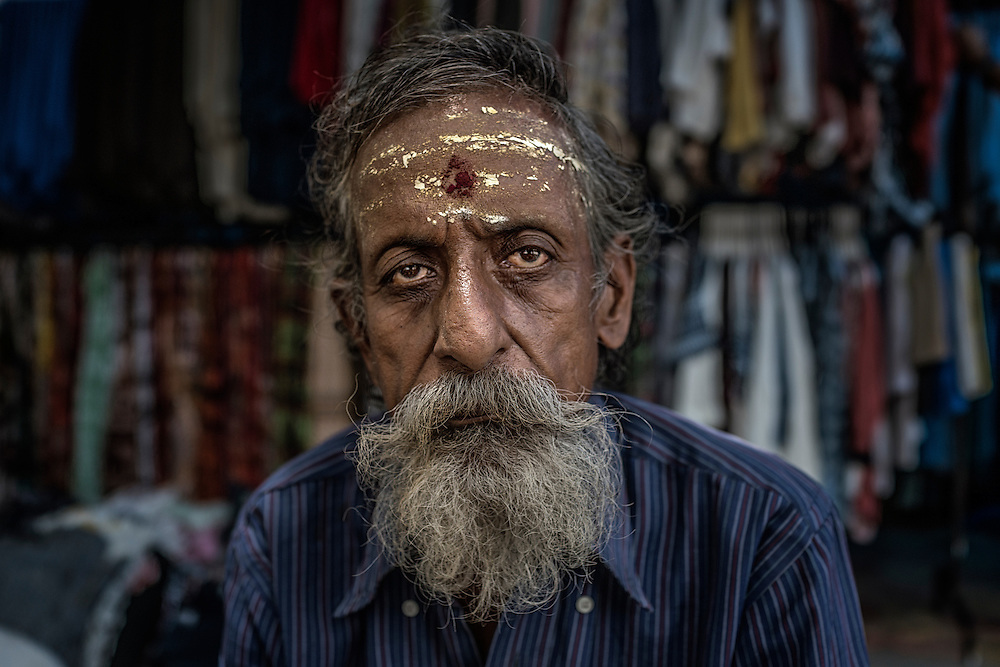 Clothes vendor after he has gone to the Arulmiga Manakula Vinayagar Temple during Ganesh Chaturthi Festival.  Pondicherry, India.