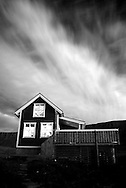 A black and white of a small wooden house and mystic clouds in Aðalvík, Hornstrandir, Iceland.