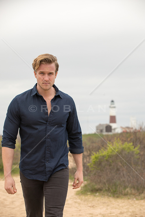 handsome rugged man walking on a dirt path by a lighthouse