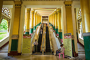 15 JUNE 2013 - YANGON, MYANMAR:  The west stairway into Shwedagon Pagoda. The Shwedagon Pagoda is officially known as Shwedagon Zedi Daw and is also called the Great Dagon Pagoda or the Golden Pagoda. It is a 99 metres (325 ft) tall pagoda and stupa located in Yangon, Burma. The pagoda lies to the west of on Singuttara Hill, and dominates the skyline of the city. It is the most sacred Buddhist pagoda in Myanmar and contains relics of the past four Buddhas enshrined: the staff of Kakusandha, the water filter of Koṇāgamana, a piece of the robe of Kassapa and eight strands of hair fromGautama, the historical Buddha. The pagoda was built between the 6th and 10th centuries by the Mon people, who used to dominate the area around what is now Yangon (Rangoon). The pagoda has been renovated numerous times through the centuries. Millions of Burmese and tens of thousands of tourists visit the pagoda every year, which is the most visited site in Yangon.  PHOTO BY JACK KURTZ