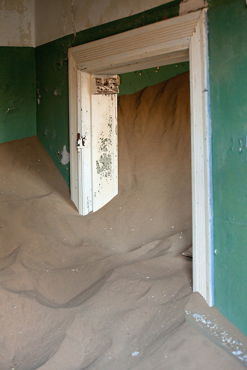 Sand fills an entire room up to near the ceiling in an abandoned home in Kolmanskop, Namibia