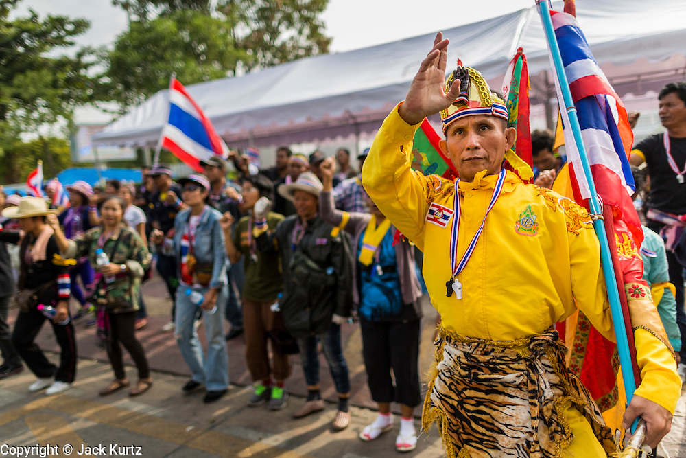 24 DECEMBER 2013 - BANGKOK, THAILAND: A Thai ultra-nationalist anti-government protestor marches past anti-government protestors blocking access to the Thai-Japan Stadium. Hundreds of anti-government protestors are camped out around the Thai-Japan Stadium in Bangkok, where political parties are supposed to register for the election on February 2. As of Dec 24, nine of the more than 30 parties were able to register. Protestors hope to prevent the election. The action is a part of the ongoing protests in Bangkok that have caused the dissolution of the elected government.      PHOTO BY JACK KURTZ