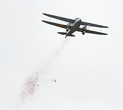 © Licensed to London News Pictures. 08/11/2015. Duxford, UK. Thousands of poppies being dropped from a Dragon Rapide plane following an official service of Remembrance and wreath laying ceremony at Imperial War Museum Duxford, Cambridgeshire on Remembrance Sunday 2015. . Photo credit: Ben Cawthra/LNP