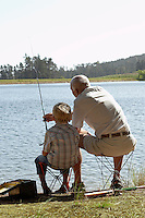 Boy (7-9) fishing with grandfather back view.