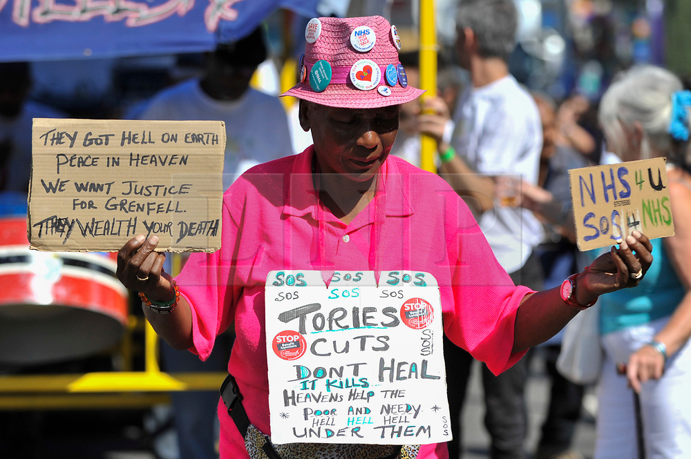 © Licensed to London News Pictures. 27/08/2017. London, UK. A woman carries signs in support of the victims of the Grenfell Tower fire during Family Day at the Notting Hill Carnival.  Over one million revellers are expected to attend Europe's biggest street party which takes place over the Bank Holiday Weekend. Photo credit : Stephen Chung/LNP