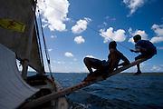 Boys balancing sailboat, dhow, off Lamu Island, Kenya, Africa