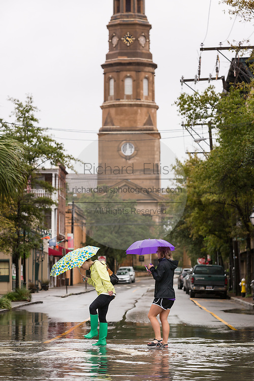 Young women walk through floodwater across Church Street past St. Philipps Church as Hurricane Joaquin brings heavy rain, flooding and strong winds as it passes offshore October 4, 2015 in Charleston, South Carolina.