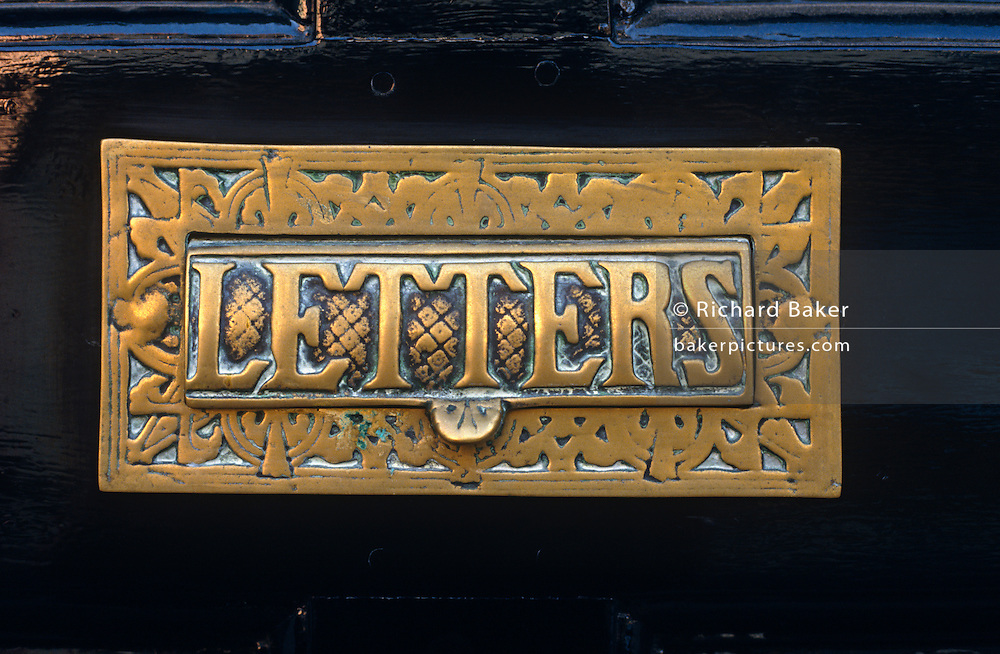 A detail of an ornate Victorian brass letter box plate. Seen in close-up, the single and plural word 'Letters' is printed in upper-case capitals on the flap that one must lift to insert postal mail from the outside of this heavy, glossy black doors in the seaside town of Lowestoft in Suffolk, England. The brass plate sits in its fitted slot and has been carefully polished these last decades to ensure it still looks as handsome as it might have some time in the Victorian era when brass door knockers and other elaborate fittings were fixed to houses, showing true quality craftsmanship - a factor largely ignored in the mass-produced products of today.