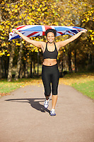 Happy young female jogger holding up British flag on pathway in park