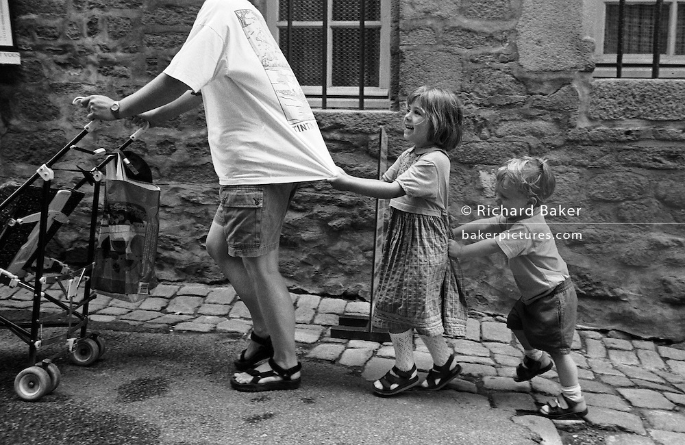 "A four year-old girl pulls at her mother's t-shirt as she pushes a pushchair uphill while her two year-old brother in turn pushes her up the incline of a street in Rennes, Brittany, France. In order of size - from tallest to smallest, they march together up the gradient of this French street, they laugh at this great game of push and pull. The three are on holiday in this town, during a vacation to Britanny. From a personal documentary project entitled ""Next of Kin"" about the photographer's two children's early years spent in parallel universes. Model released."