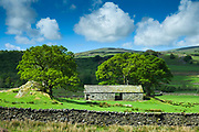 Stone barn and puffy clouds in blue sky near the River Duddon with Whitefell in the background in the Lake District, Cumbria, England