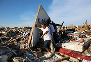 Men lift a walk in an effort to salvage belongings from their tornado-ravaged homes in Moore, Oklahoma May 21, 2013. A massive tornado tore through a suburb of Oklahoma City, wiping out whole blocks and killing at least 24.   REUTERS/Rick Wilking (UNITED STATES)