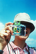 A girl holding a colourful Lomo sampler camera, Glastonbury Festival, UK 1999