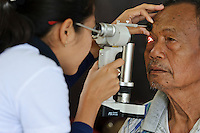 Cataract surgery patient having his eye checked the day after surgery, Bali, Indonesia.