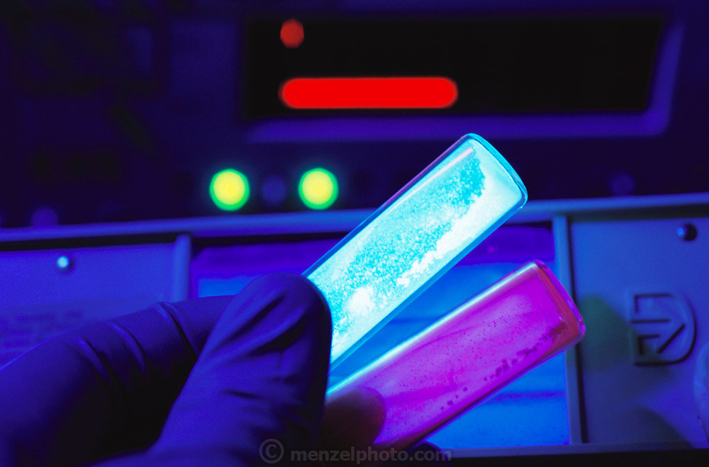 Mountain View, California.Vials of chemicals known as P.A.H. (Polycyclic Aromatic Hydrocarbons) luminesce in ultraviolet light. These molecules, naturally occuring throughout the depths of space, are believed by these and and other researchers to be possible origins of life on earth. P.A.H.s have been found to become chemically modified when surrounded by ice and exposed to ultraviolet radiation -- a situation likely to occur in space.iOnce molecularly altered, the modified P.A.H.s closely resemble known organic molicules that are found in abundance on earth. Thus P.A.H.s may be found to be the first stage in a chain of molecules that led to life on earth. Researchers at NASA/Ames are simulating the conditions in space in order to study these alterations in the molecular structure of P.A.H.s. They also track P.A.H.s as they travel through interstellar space towards developing solar systems where they may become transformed into the seeds of life, all to hypothesize about the origins of life on earth..[1999]