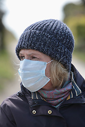 Covid 19 - Woman wearing a face mask while outdoors. Dorset, UK March 2020. Posed by model