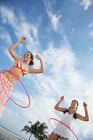 Teenage girls (16-17) playing with hoola hoop on beach low angle view