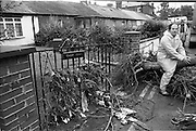 "Flooding at the Dodder..1986..26.08.1986..08.26.1986..28th August 1986..As a result of Hurricane Charly (Charlie) heavy overnight rainfall was the cause of severe flooding in the Donnybrook/Ballsbridge areas of Dublin. In a period of just 12 hours it was stated that 8 inches of rain had fallen. The Dodder,long regarded as a ""Flashy"" river, burst its banks and caused great hardship to families in the 300 or so homes which were flooded. Council workers and the Fire Brigades did their best to try and alleviate some of the problems by removing debris and pumping out some of the homes affected..Note: ""Flashy"" is a term given to a river which is prone to flooding as a result of heavy or sustained rainfall...Image of a workman taking a rest,sitting on an uprooted tree, at the point where the road subsided."