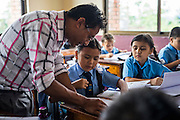Usha (name changed), aged 10, discusses her work with her teacher in her classroom in SOS Children's Villages Sanothimi, Bhaktapur, Nepal on 2 July 2015. Usha's entire family perished when her house collapsed in the earthquake on 25th April 2015. Usha is now well integrated into her new family and school. Photo by Suzanne Lee for SOS Children's Villages