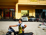 "13 FEBRUARY 2019 - SIHANOUKVILLE, CAMBODIA: A worker at the BWin Casino, a newly opened casino in downtown Sihanoukville, waits to take a co-worker home after their overnight shift in the casino. There are about 80 Chinese casinos and resort hotels open in Sihanoukville and dozens more under construction. The casinos are changing the city, once a sleepy port on Southeast Asia's ""backpacker trail"" into a booming city. The change is coming with a cost though. Many Cambodian residents of Sihanoukville  have lost their homes to make way for the casinos and the jobs are going to Chinese workers, brought in to build casinos and work in the casinos.      PHOTO BY JACK KURTZ"