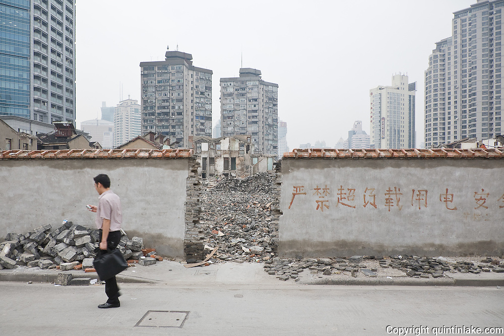 """Vanishing Shanghai II. An area of low-rise housing is demolished for development. The writing on the wall reads, """"Overusage of Electricity Prohibited"""". Shanghai, China, 2007"""