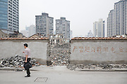 "Vanishing Shanghai II. An area of low-rise housing is demolished for development. The writing on the wall reads, ""Overusage of Electricity Prohibited"". Shanghai, China, 2007"