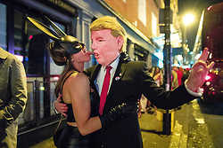 © Licensed to London News Pictures . 28/10/2018. Manchester, UK. A woman sticks her tongue out to kiss a man dressed as Donald Trump , on Peter Street , in Manchester City Centre . Revellers on a night out , many in fancy dress , on the weekend before Halloween . Photo credit: Joel Goodman/LNP