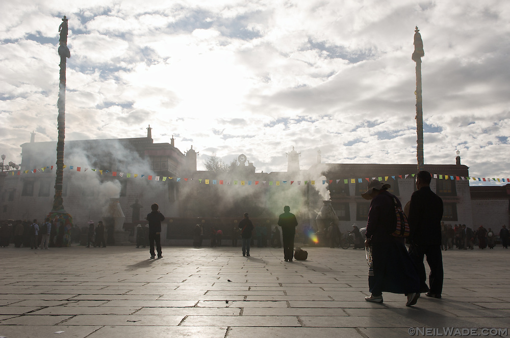 Pilgrims and merchants walk and pray in the juniper smoke on The Barkor at The Jokang Monastery, Lhasa, Tibet.