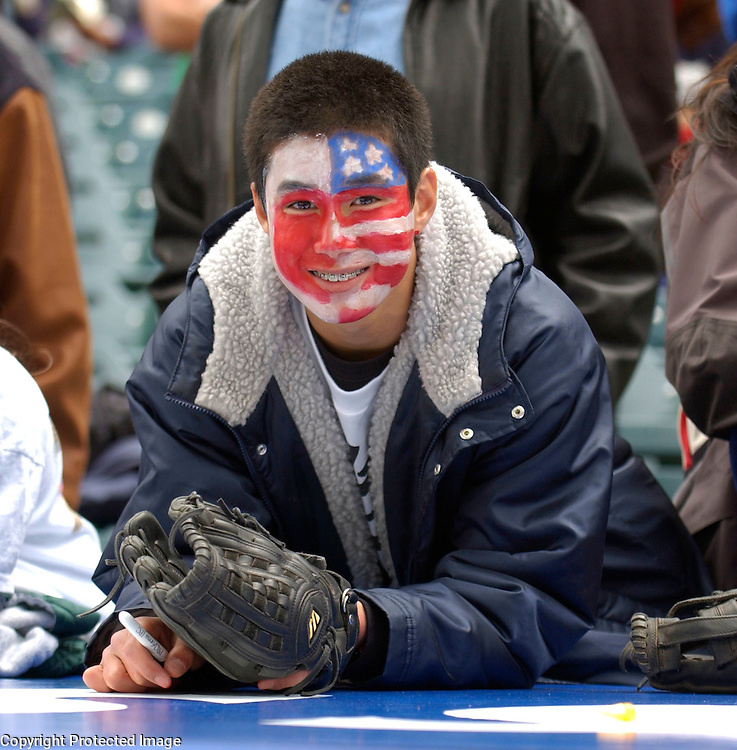 A fan of Team Japan and Team USA has his face painted with both colors of Japan and the USA watching pregame warmups before the start of Round 2 Japan vs USA at Angel Stadium of Anaheim.